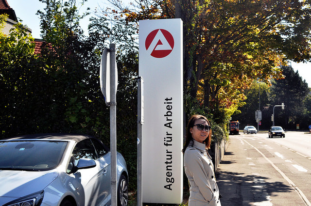 Young woman standing in front of the signboard of the employment agency in Boeblingen, Germany.
