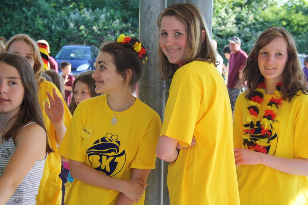 Girls wearing yellow t-shirts and paper flower chains in the colours of the German flag