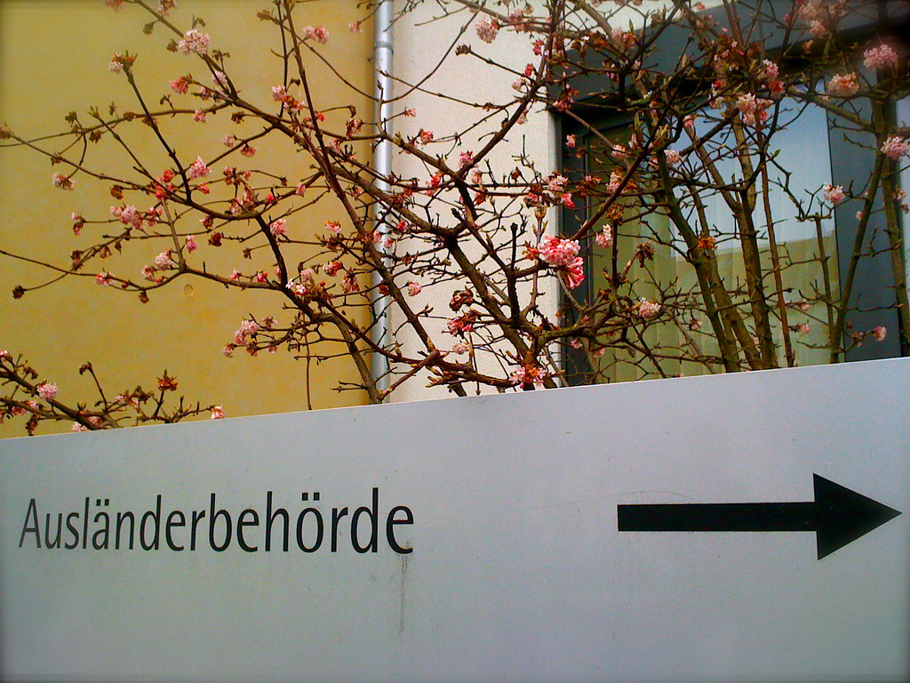 A signpost with the inscription 'Ausländerbehörde', German for Aliens Registration Office, and an arrow going to the right.
